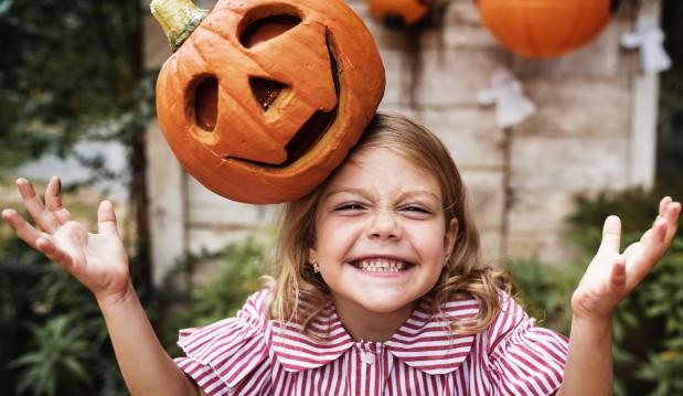 Halloween a Triora bambina che gioca con una zucca intagliata