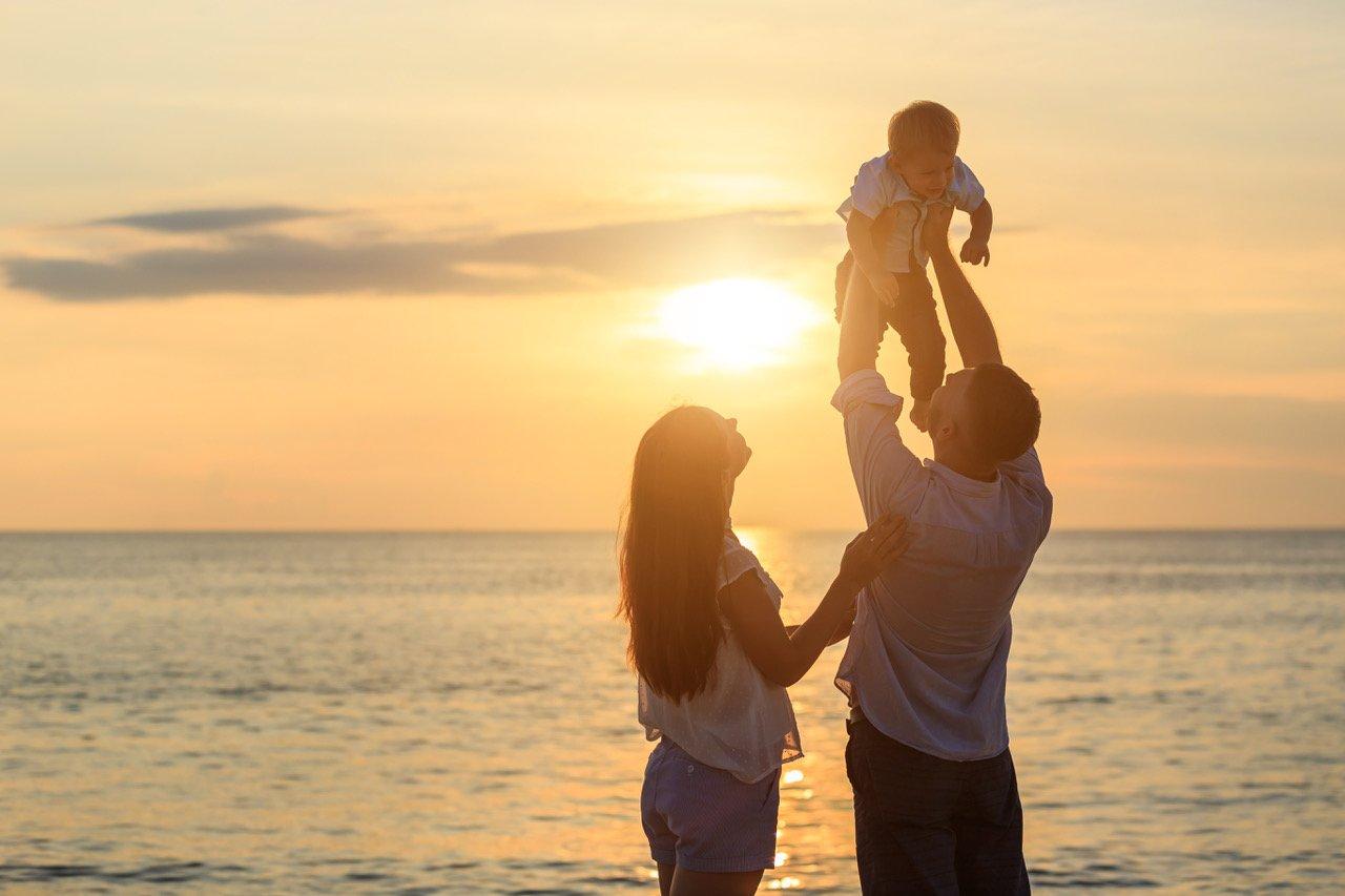 Famiglia in spiaggia al tramonto anche durante l'ultimo giorno di vacanza grazie al Late Check Out